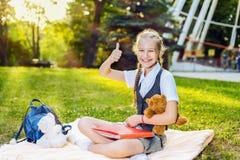 女小学生学生愉快的微笑的显示的赞许坐一条毯子在公园在一好日子 少年拿着一个熊玩具 免版税库存照片