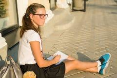 女小学生少年在笔记本写 日志女孩,秘密, 库存图片