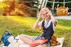 女小学生快乐的微笑的和显示的好标志 学生在公园坐有熊是的软的玩具玩具的一条毯子 免版税库存图片