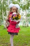 女小学生打扮与花束 免版税库存照片