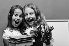 女小学生拿着书和文具在绿色背景 有愉快和惊奇的面孔拥抱的女孩 库存照片