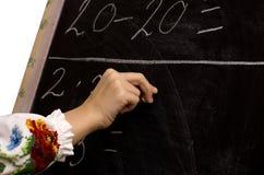 女小学生文字的手在黑板的 免版税库存照片
