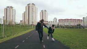 女小学生是握母亲` s手的冰鞋路辗 在体育场的秋天活动 影视素材