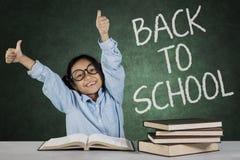 女小学生显示与回到学校词的好标志 库存照片