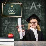 女小学生的综合图象有毕业长袍和拿着的她的文凭 图库摄影
