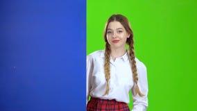 女小学生看从一个蓝色委员会的后面并且显示得好 绿色屏幕 股票录像