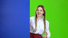 女小学生看从一个蓝色委员会的后面并且显示赞许 绿色屏幕 股票视频