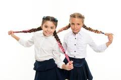 女小学生穿正式校服 有辫子的姐妹女孩准备好学校 学校时尚概念 是 免版税图库摄影