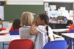 女小学生耳语入她的朋友耳朵在教室在学校 免版税库存照片