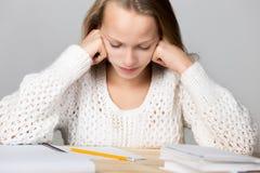女小学生让烦恼与坚韧学习 免版税库存照片