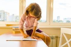 女小学生,坐在与书的桌上和写在笔记本的8年的女孩 学校、教育、知识和孩子 免版税库存照片