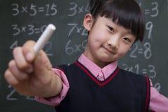 女小学生画象在拿着白垩的黑板前面的 免版税库存图片