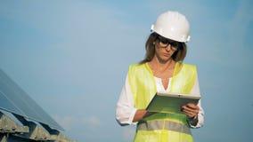 女工在她的手上走与一台膝上型计算机并且看太阳设施 股票录像