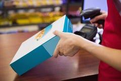 女工扫描谷类食品盒 库存图片