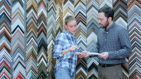 女工谈话与关于画框细节的顾客在工作室 免版税库存图片