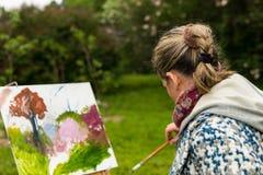 女性不分心的艺术家paintig最后一笔在公园 库存照片