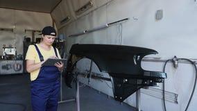 女性与在车库的一种数字式片剂一起使用汽车修理的 股票视频
