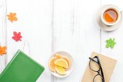 女性与日志、镜片、书、茶杯子、甜点和毛毡装饰的书桌工作区平的位置 免版税库存图片
