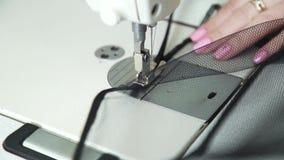 女性与缝纫机的裁缝缝合的织品的准确手特写镜头  股票录像