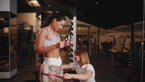 女性个人教练员测量腰部、胸象和臀部要丢失重量的女性的 股票视频