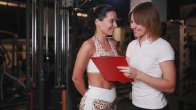 女性个人教练员谈话与健身房的一个妇女客户使用笔记的一种片剂 股票录像