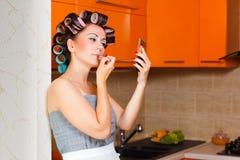 女性中年主妇在厨房里绘她的嘴唇 免版税库存图片