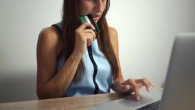 女性举行的信用卡和在家使用在互联网上的手提电脑购买在线事务的购物和 股票录像