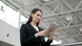年轻女性乘客旅行家在使用她的片剂计算机的机场,当以后时等待飞行,女商人 免版税库存照片