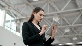 年轻女性乘客旅行家在使用她的片剂计算机的机场,当以后时等待飞行,女商人 免版税图库摄影