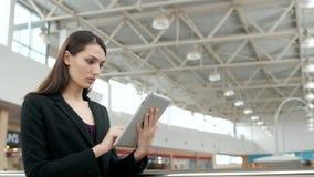 年轻女性乘客旅行家在使用她的片剂计算机的机场,当以后时等待飞行,女商人 库存图片
