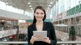 年轻女性乘客旅行家在使用她的片剂计算机的机场,当以后时等待飞行,女商人 免版税库存图片