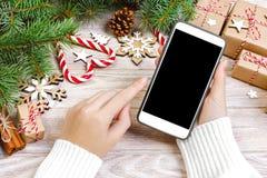 女性买家做命令在智能手机屏幕有拷贝空间的 圣诞节在线购物 妇女xmas的购买礼物 冬天 图库摄影