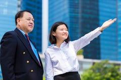 年轻女性亚裔看一个方向的执行委员和资深亚洲商人 免版税库存照片