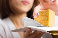 女性亚洲人吃着焦糖蛋糕用手 免版税库存照片