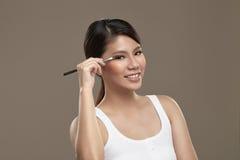 女性亚洲申请的眼影 免版税图库摄影