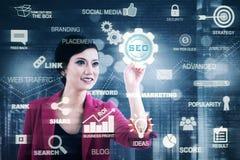 女性企业家按SEO按钮 图库摄影