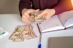 女性会计在工作场所考虑美元 免版税库存照片