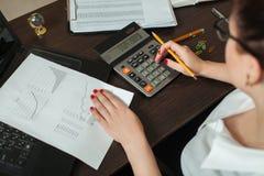 年轻女性会计在计算器考虑 库存图片