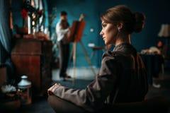 女性伪装者,反对画架的画家在背景 免版税库存图片