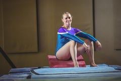 女性体操运动员坐在健身房的大楔子 库存图片