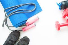 女性体育和瑜伽设备平的位置在白色背景的 免版税库存照片