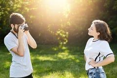 年轻女性佩带的摆在秘密审议的T恤杉和牛仔裤摄影师 与减速火箭的照相机的年轻有天才的男性拍摄prett的 图库摄影
