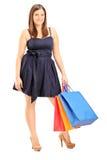 年轻女性佩带的礼服和拿着购物袋 免版税库存照片