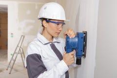 女性使用力量沙磨机的石膏工铺沙的墙壁 免版税库存图片