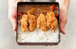 女性使用手对拿着和递日本咖喱饭顶部盘与炸鸡和菜的 免版税库存照片