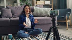 女性使用打手势的智能手机的vlogger记录的录影在家谈话和 股票视频