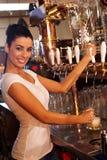 女性侍酒者轻拍的桶装啤酒在客栈 免版税库存照片