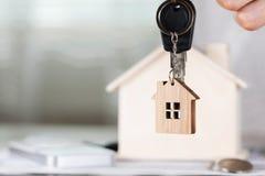 女性保留在一个关键挂衣架的房子钥匙在一木hous前面 库存图片
