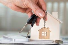女性保留在一个关键挂衣架的房子钥匙在一木hous前面 图库摄影