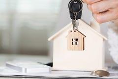 女性保留在一个关键挂衣架的房子钥匙在一木hous前面 免版税库存照片